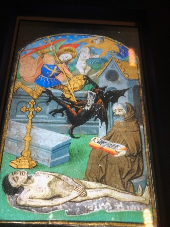 "Seven miniatures from a breviary (displayed on the screen of a tablet), c1470, Rouen, McGill University Library. Illustration of the psalter: ""a corpse in a cemetery above which takes place a fight between Saint Michael and the Devil for the soul of the dead man. Meanwhile, a hermit monk is praying, with a prayer book open on his knees"" (Office of the Dead)."