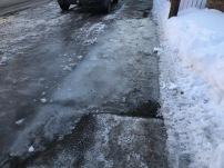 Accumulation d'eau glacée sur le trottoir où l'épandage d'abrasif n'est pas fait assez fréquemment